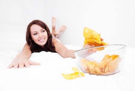 weight gain: happy young woman eating potato chips in bed at home