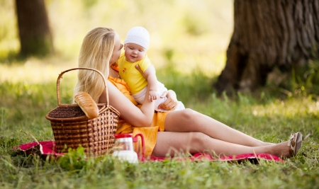 young mother and baby having a picnic outdoor on a warm summer day photo