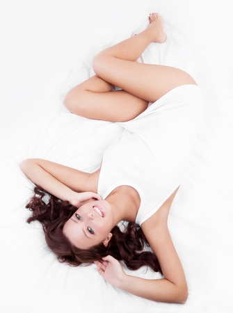 slim young brunette woman  on the white linen in bed at home, top view Stock Photo - 14405878