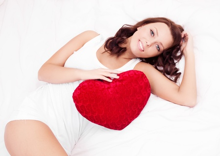 slim young brunette woman with a heart-shaped pillow in bed at home, top view Stock Photo - 14405882