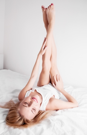 happy woman  on the white linen in bed at home  Stock Photo - 14994900