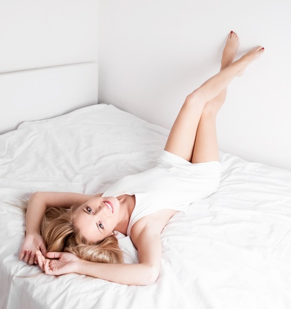 happy woman  on the white linen in bed at home  Stock Photo - 14994896