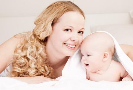 Mutter schlang ihre vier Monate alten Baby in Handt�cher nach der Dusche zu Hause im Bett Lizenzfreie Bilder - 14996122