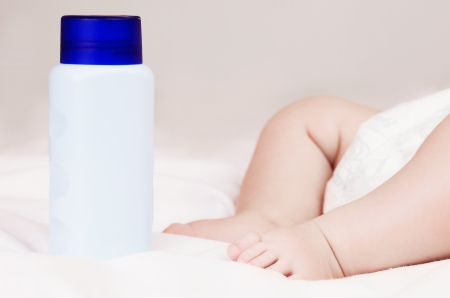 baby powder near the sleeping four month old baby in bed at home photo