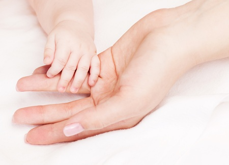 body parts: hands of mother and baby, in bed at home