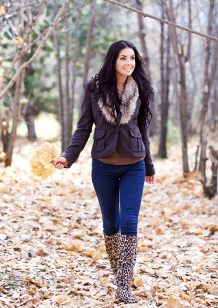 beautiful stylish woman walking in the autumn park