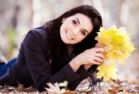 秋の公園で黄色の葉を持つ美しい女性