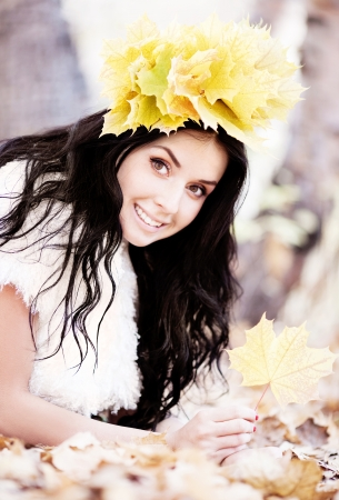 outsides: beautiful brunette woman wearing a diadem of yellow maple leaves in the autumn park