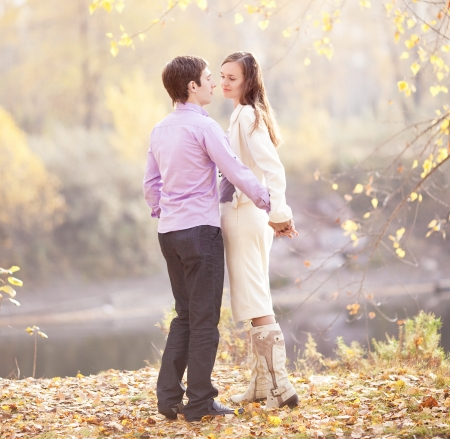 happy young couple spending time outdoor in the autumn park   photo