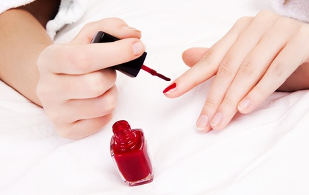 hands of a woman applying red nail polish photo