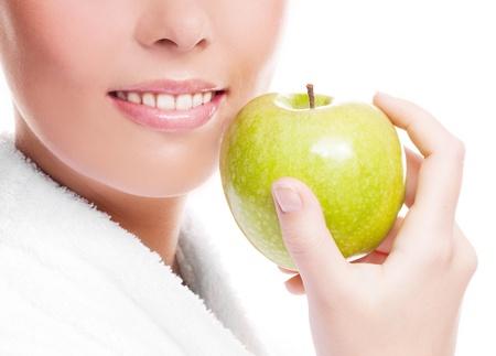 白い背景に対して隔離される、リンゴを持った女性の健康な白い歯、手、顔のクローズ アップ