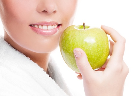 closeup of the face, hands and healthy white teeth of a woman holding an apple, isolated against white background  Stock Photo
