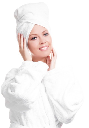 beautiful young woman wearing a towel and a white bathrobe  massaging her face, isolated against white background Standard-Bild