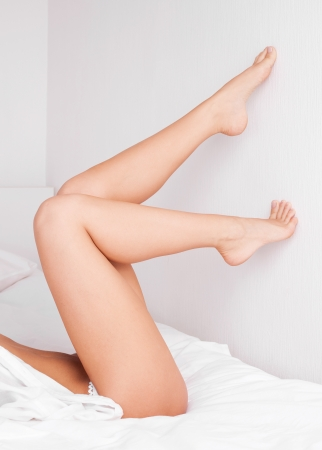 legs of a sexy slim young  woman in bed at home photo