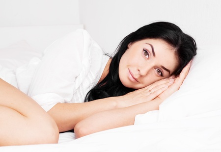 young brunette woman in bed at home  Stock Photo - 15026196