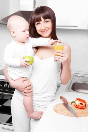 beautiful  young woman drinking orange juice and holding her baby eating an apple in the kitchen photo