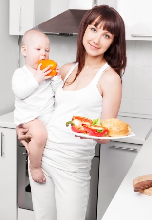 beautiful  young woman holding her baby and cutting vegetables for the salad in the kitchen photo