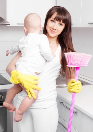 beautiful  young woman holding her baby and cleaning the furniture in the kitchen photo