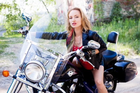 attractive woman biker posing on her motorcycle photo