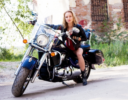 彼女のバイクにポーズをとって魅力的な女性バイカー