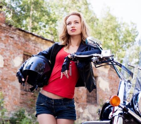 biker atractiva mujer que sostiene un casco y que presenta con su motocicleta Foto de archivo