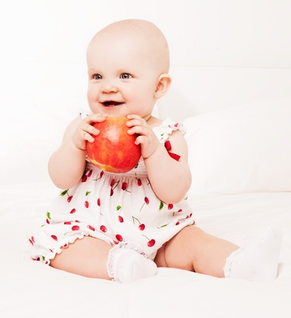1 year old: one year old baby eating an apple, in bed at home