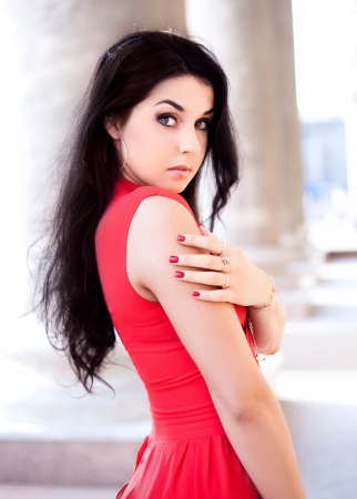 appealing attractive: beautiful young brunete woman wearing a red dress in the street