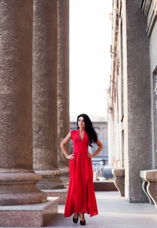beautiful young brunete woman wearing a red dress, in the street photo