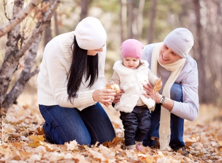 happy young family with their daughter spending time outdoor in the autumn park (focus on the baby) Stock Photo - 15264676