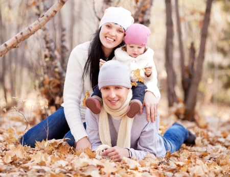 happy young family with their daughter spending time outdoor in the autumn park  (focus on the man) Banque d'images