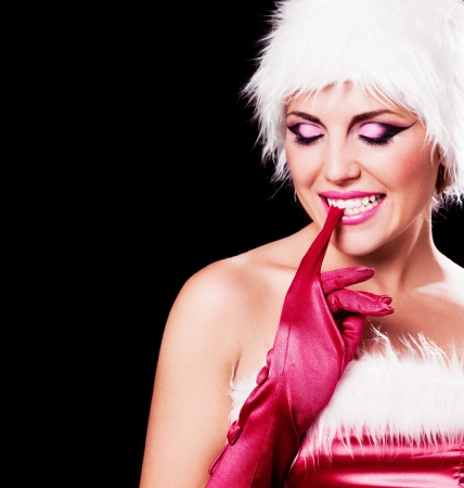 beautiful young woman dressed as Santa, isolated against black background, copyspace for your text to th left Stock Photo - 15367485