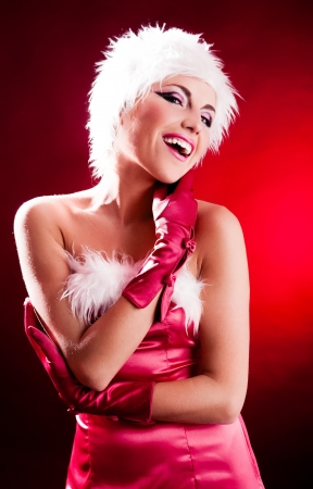 santa helper: beautiful young woman dressed as Santa, isolated against black background