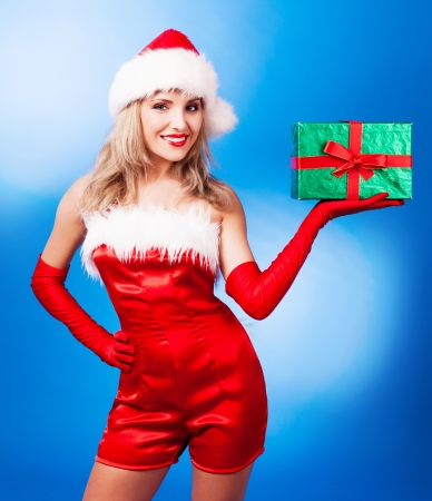 beautiful young woman dressed as Santa, against blue studio background photo