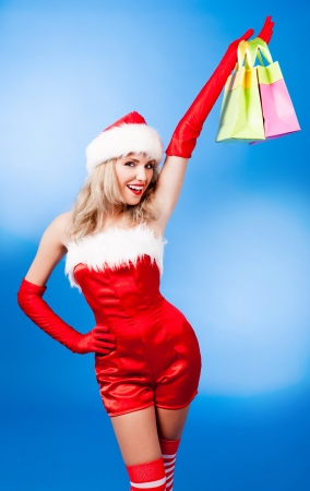 red gloves: beautiful young woman dressed as Santa, against blue studio background