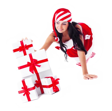 beautiful young brunette woman dressed as Santa with a lot of presents, isolated against white background photo