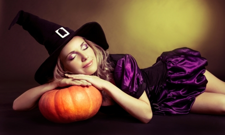 beautiful sleeping witch with a pumpkin, against yellow studio background photo