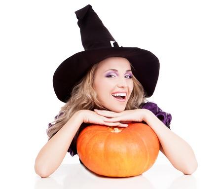 calabazas de halloween: bruja joven feliz con una calabaza que se sienta a la mesa, aislada en el fondo blanco