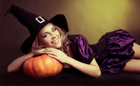 happy young  witch with  a pumpkin,  against yellow studio background photo
