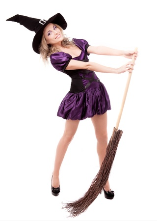 happy young witch with a broom, isolated on white studio background photo