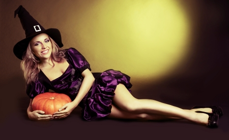 sexy fairy: happy young  witch with  a pumpkin, against yellow studio background
