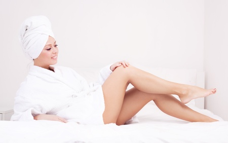 beautiful young woman wearing a towel and a white bathrobe in bed at home photo