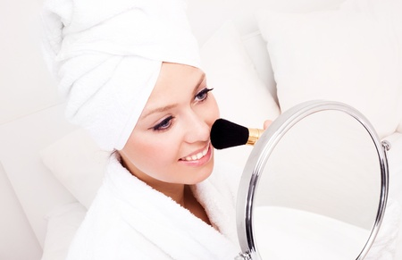 head home: beautiful young woman wearing a towel and a white bathrobe and holding a brush and mirror, isolated against white background Stock Photo