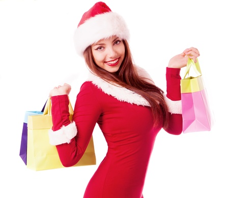sexy costume: beautiful young brunette woman dressed as Santa with shopping bags, isolated against white background