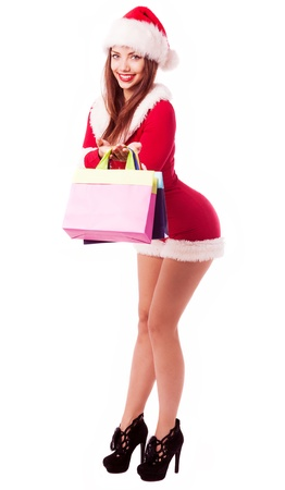 santa helper: beautiful young brunette woman dressed as Santa with shopping bags, isolated against white background