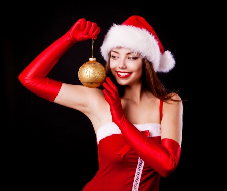 santa helper: beautiful young brunette woman dressed as Santa with a Christmas toy  , isolated against blackbackground