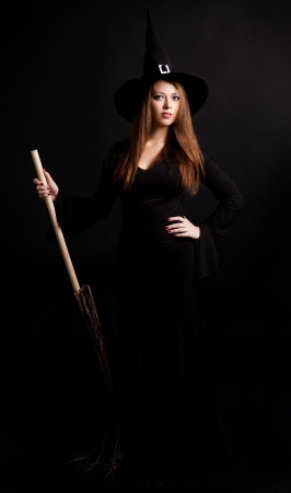 young  witch with  a broom, against dark studio background photo