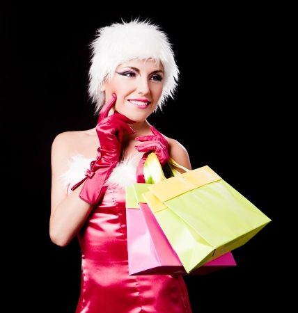 beautiful young woman dressed as Santa holding paper bags with presents, isolated against black background photo