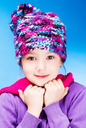 seven year old: seven year old girl wearing a warm winter hat, against blue studio background