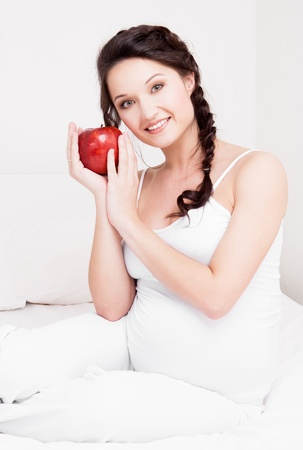 beautiful young pregnant woman eating an apple in bed at home   photo