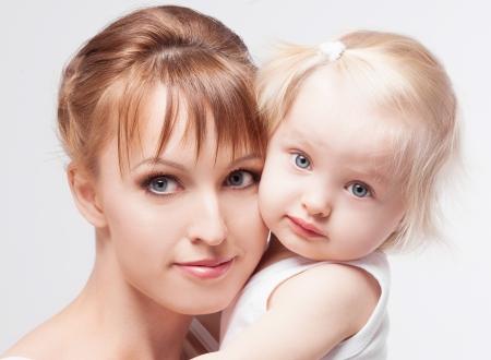 白のスタジオの背景に、彼女は赤ん坊を持つ若い母親 写真素材